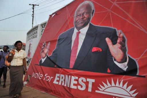 A woman walks past a poster of Sierra Leone's President Ernest Bai Koroma on November 14 in Freetown, ahead of elections