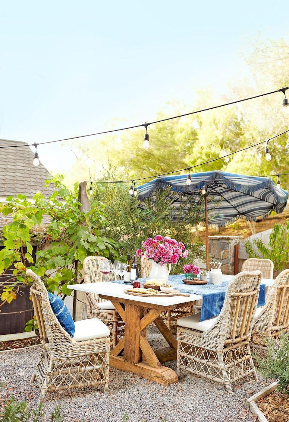 """<p>Make your small space feel even cozier by stringing lights from one side of the yard to the other. That way, you won't have to use up coveted floor space with standing lamps. </p><p><strong>RELATED: </strong><a href=""""https://www.goodhousekeeping.com/home/gardening/tips/g1226/small-outdoor-space-decor/"""" rel=""""nofollow noopener"""" target=""""_blank"""" data-ylk=""""slk:How to Decorate Your Small Patio"""" class=""""link rapid-noclick-resp"""">How to Decorate Your Small Patio </a></p>"""