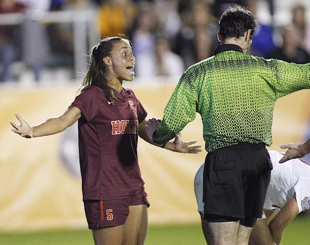 Virginia Tech's Jazmine Reeves, left, questions a call by an official during the second half of an NCAA college soccer semifinal match against Florida State at the Women's College Cup tournament in Cary, N.C., Friday, Dec. 6, 2013. (AP Photo/Ellen Ozier)