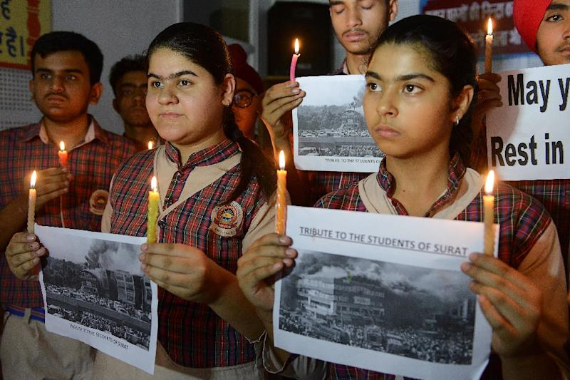 Indian students hold candles as they pay tribute to the students died in the fire in Surat (AFP Photo/NARINDER NANU)