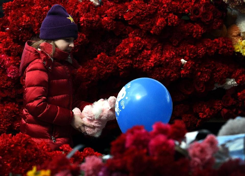 A girl lays a toy for victims of the air crash, outside the Rostov-on-Don airport entrance on March 20, 2016 (AFP Photo/Vasily Maximov)