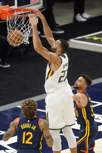 Utah Jazz center Rudy Gobert (27) dunks as Golden State Warriors' Kelly Oubre Jr. (12) and Stephen Curry, right, defend during the first half of an NBA basketball game Saturday, Jan. 23, 2021, in Salt Lake City. (AP Photo/Rick Bowmer)
