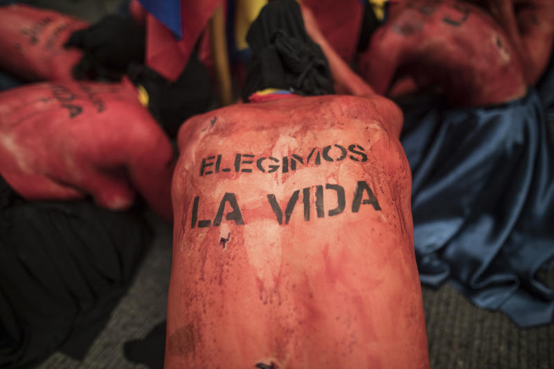 """Women perform during march against the murders of activists, in Bogota, Colombia, Friday, July 26, 2019. Colombians took to the streets to call for an end to a wave of killings of leftist activists in the wake of the nation's peace deal. The text written on their backs reads in Spanish """"We Choose Life."""" (AP Photo/Ivan Valencia)"""