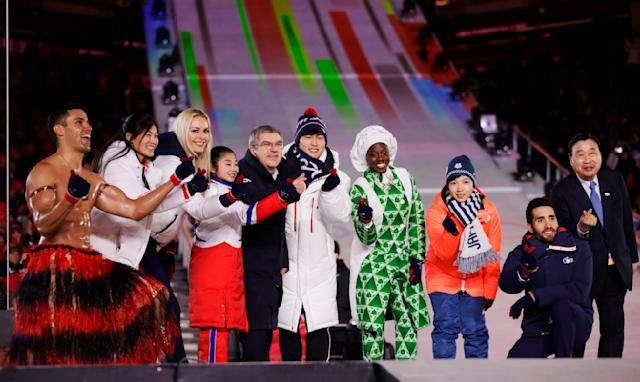 Athletes from various nations including Pita Taufatofua, of Tonga, at left, United States' Lindsey Vonn, third from left, and Thomas Bach, president of the International Olympic Committee, fifth from left, pose for photos during the closing ceremony of the 2018 Winter Olympics in Pyeongchang, South Korea, Sunday, Feb. 25, 2018. (AP Photo/Kirsty Wigglesworth)