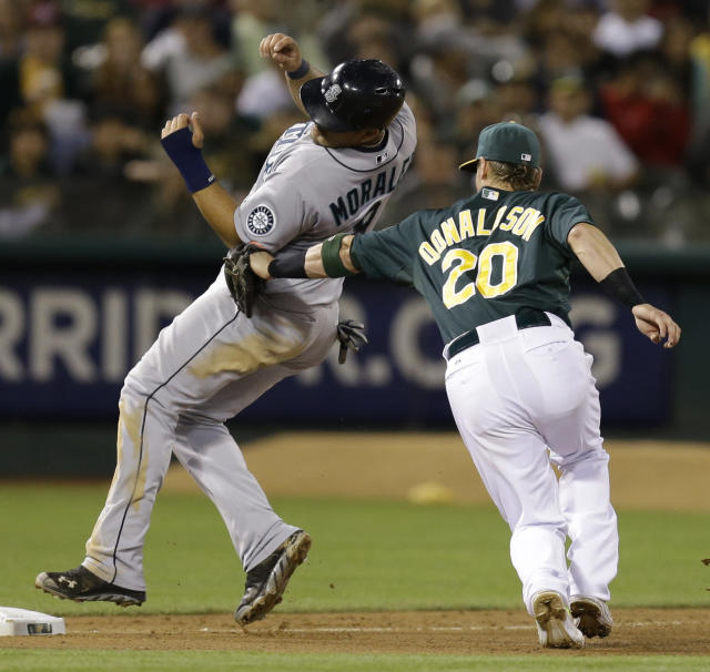 Seattle Mariners' Kendrys Morales, left, is tagged out by Oakland Athletics third baseman Josh Donaldson in the seventh inning of a baseball game Monday, Aug. 19, 2013, in Oakland, Calif. Morales was trying to advance on a hit by Justin Smoak. (AP Photo/Ben Margot)