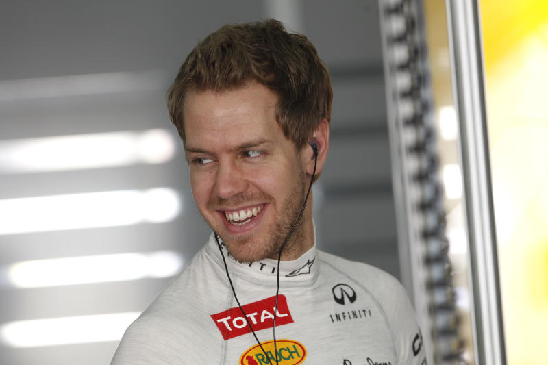 Red Bull driver Sebastian Vettel of Germany smiles in the pits during the first free practice ahead the Bahrain Formula One Grand Prix at the Formula One Bahrain International Circuit in Sakhir, Bahrain, Friday, April 20, 2012. Authorities in Bahrain have stepped up security around the Formula One circuit at the start of the controversial Grand Prix racing weekend. (AP Photo/Luca Bruno)