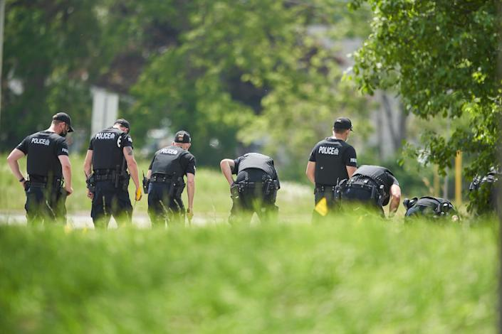 A line of police officers look for evidence at the scene of a car crash in London, Ontario on Monday, June 7, 2021. Police say multiple people have died after several pedestrians were struck by a car Sunday night.