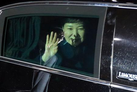 South Korea's ousted leader Park Geun-hye sitting inside a vehicle waves to her supporters upon her arrival to her private house in Seoul