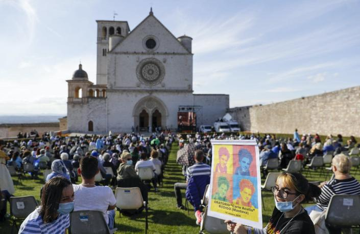 """<span class=""""caption"""">The ceremony for the beatification of Carlo Acutis, an Italian boy who died in 2006 of leukemia, is held Oct. 10 in front of the St. Francis Basilica in Assisi, Italy.</span> <span class=""""attribution""""><a class=""""link rapid-noclick-resp"""" href=""""https://newsroom.ap.org/detail/ItalyTeenBeatification/ab6eac9a939f4b388534c5642956b57d/photo?Query=Carlo%20AND%20Acutis&mediaType=photo&sortBy=&dateRange=Anytime&totalCount=27&currentItemNo=13"""" rel=""""nofollow noopener"""" target=""""_blank"""" data-ylk=""""slk:AP Photo/Gregorio Borgia"""">AP Photo/Gregorio Borgia</a></span>"""