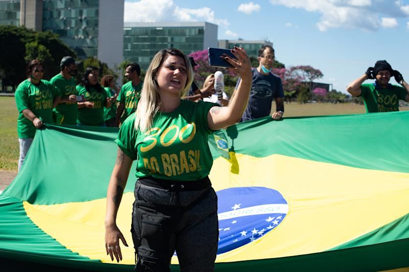 """BRASILIA, BRAZIL - JUNE 13: Sara Winter, the leader of the extreme right group """"300 do Brasil"""" and supporter of Brazilian President Jair Bolsonaro, films with her cell phone during protest against the President amidst the coronavirus (COVID-19) pandemic at the Esplanada dos Ministérios on June 13, 2020 in Brasilia.Sara Winter was arrested on June 15 by the Federal Police as part of an investigation into the financing of anti-democratic protests.(Photo by Andressa Anholete/Getty Images)"""