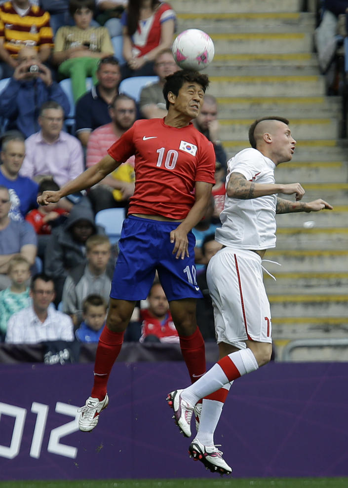 South Korea's Park Chu-young, left, battles for the ball against Switzerland's Michel Morganella during the group B men's soccer match between South Korea and Switzerland at the London 2012 Summer Olympics, in Coventry, England, Sunday, July 29, 2012. (AP Photo/Hussein Malla)