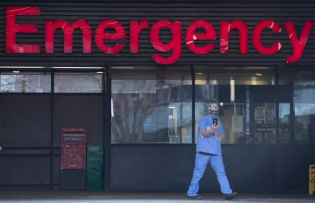 A health-care worker is seen outside the Emergency dept. of the Vancouver General Hospital in Vancouver on March 30. A doctor at the hospital says its intensive care unit is more stressed than ever before. (Jonathan Hayward/The Canadian Press - image credit)