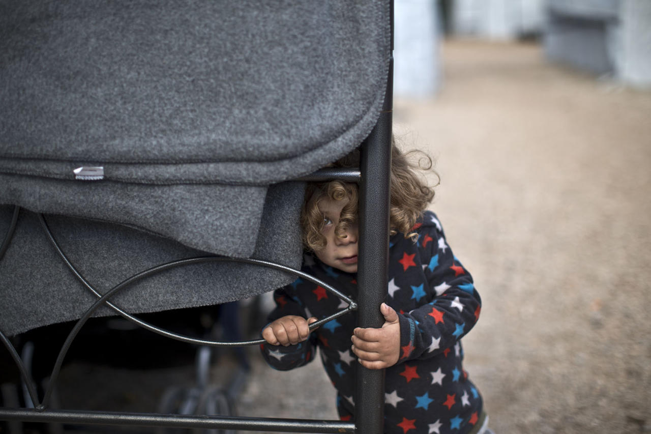 <p>Refugee Moustafa Abdulrahman, 2, from Kobani, Syria, peeks out while standing outside his family's shelter at the Ritsona refugee camp about 86 kilometers (53 miles) north of Athens, Jan. 5, 2017. (Photo: Muhammed Muheisen/AP) </p>
