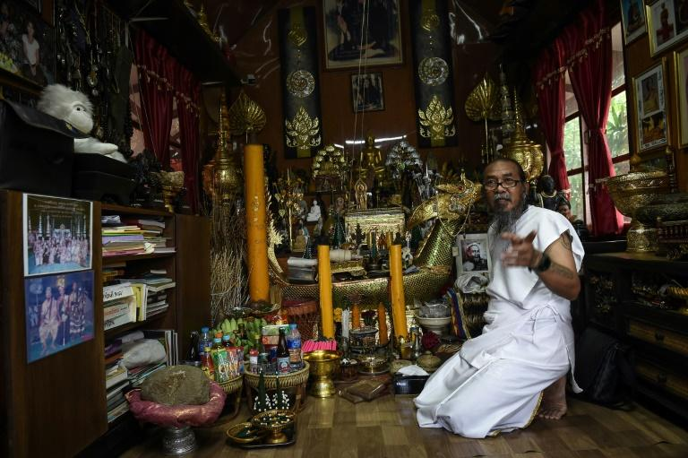 Surrounded by a cornucopia of glittering Buddha statues, eerie dolls and other spiritual trinkets, the 57-year-old Thai 'hermit' Toon uses powders and ointments to conduct his 'good luck' ritual