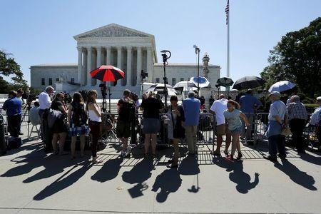 Tourists watch as television news crews report on decisions handed down on the last day of the term at the U.S. Supreme Court building in Washington June 29, 2015. REUTERS/Jonathan Ernst