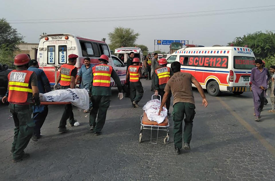 In this handout photo released by Punjab Province's Emergency Service Rescue 11222, shows rescue workers removing bodies at the site of a deadly bus accident near Dera Ghazi Khan, Pakistan, Monday, July 19, 2021. The speeding bus carrying mostly laborers traveling home for a major Muslim holiday rammed into a container truck on a busy highway in central Pakistan, killing and injuring dozens, police and rescue officials said. (Emergency Service Rescue 1122 via AP)