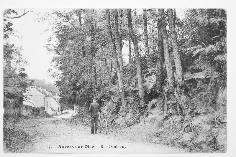 A faded picture postcard featuring a man standing next to a bicycle on a back street of the village of Auvers-sur-Oise