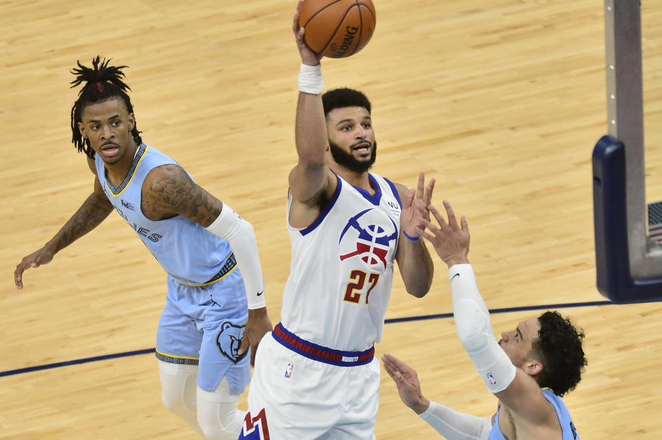 Denver Nuggets guard Jamal Murray (27) shoots against Memphis Grizzlies guards Dillon Brooks, right, and Ja Morant in the second half of an NBA basketball game Friday, March 12, 2021, in Memphis, Tenn. (AP Photo/Brandon Dill)