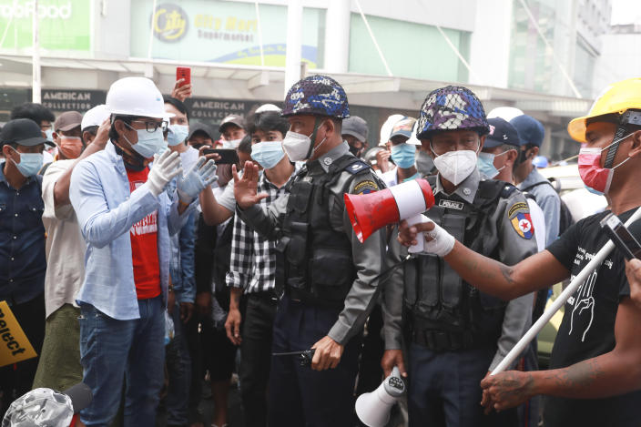 Police officers talk with protesters during a demonstration against the military coup in Yangon, Myanmar, Friday, Feb. 26, 2021. Security forces in Myanmar's largest city of Yangon have fired warning shots and beat truncheons against their shields while moving to disperse more than 1,000 anti-coup protesters. (AP Photo)