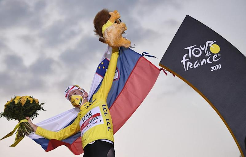Team UAE Emirates rider Tadej Pogacar wearing the overall leader's yellow jersey celebrates on the podium after winning the 107th edition of the Tour de France.
