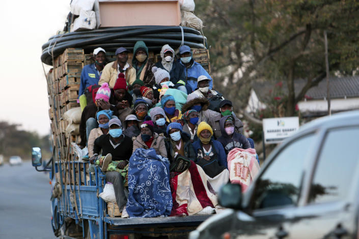 FILE - In this July, 22, 2020, file photo, an open truck carries farmers wearing face masks on the first day of the curfew in Harare, Wednesday, July, 22, 2020. Africa's confirmed coronavirus cases have surpassed 1 million, but global health experts tell The Associated Press the true toll is several times higher. (AP Photo/Tsvangirayi Mukwazhi, File)