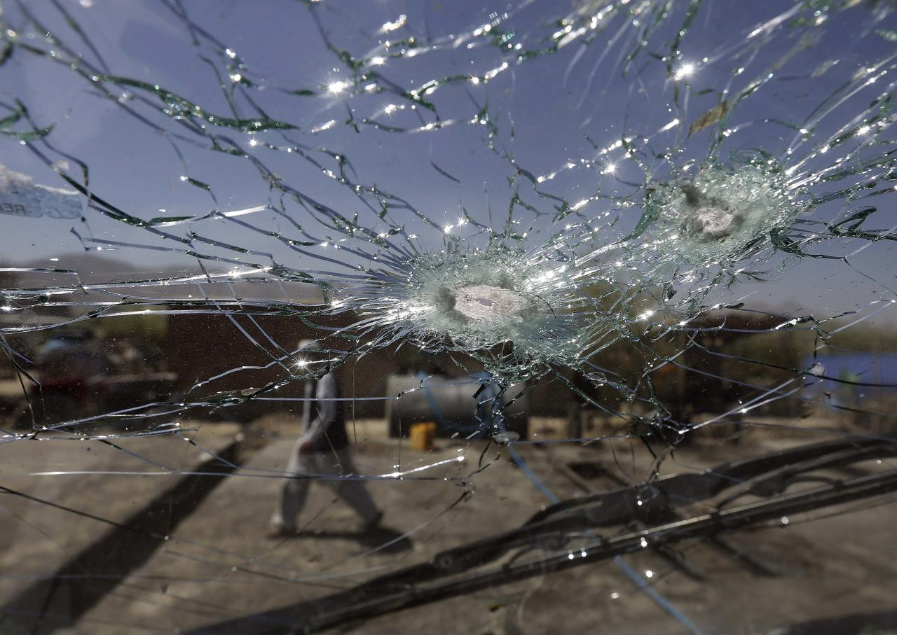 An Afghan man walks next to the cracked side window of a vehicle after was hit by a remote-controlled bomb in Kabul July 15, 2014. A remote-controlled bomb planted at the side of a road hit a government employee's vehicle, killing two people and wounding five, a police officer said. REUTERS/Omar Sobhani (AFGHANISTAN - Tags: CIVIL UNREST POLITICS CRIME LAW)