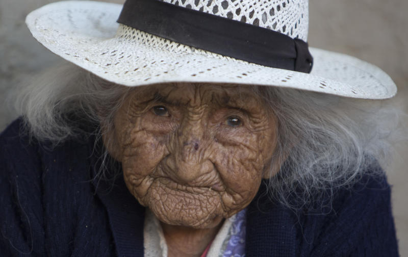 Julia Flores Colque eyes the camera while sitting outside her home in Sacaba, Bolivia, Thursday, Aug. 23, 2018. Her national identity card says Flores Colque was born on Oct. 26, 1900 in a mining camp in the Bolivian mountains. At 117 and just over 10 months, she would be the oldest woman in the Andean nation and perhaps the oldest living person in the world. (AP Photo/Juan Karita)