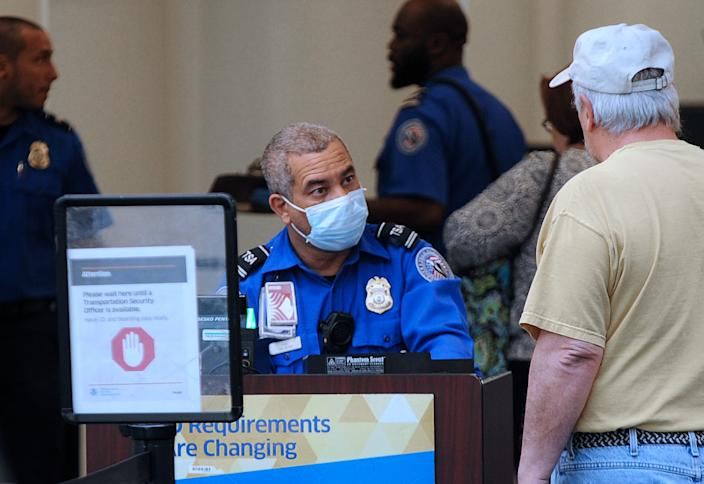 A TSA officer wears a protective mask while screening travellers at Orlando International Airport. (Paul Hennessy/Echoes Wire/Barcroft Media via Getty Images)