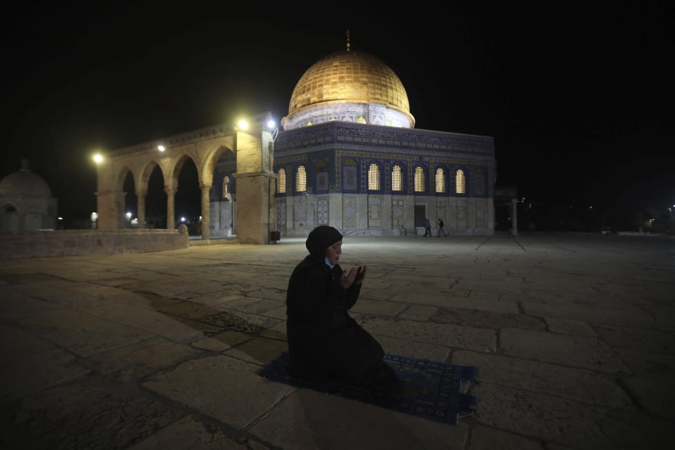 A muslim woman pray next to the Dome of the Rock Mosque in the Al Aqsa Mosque compound in Jerusalem's old city, Sunday, May 31, 2020.The Al-Aqsa mosque in Jerusalem, the third holiest site in Islam, reopened early Sunday, following weeks of closure aimed at preventing the spread of the coronavirus. (AP Photo/Mahmoud Illean)