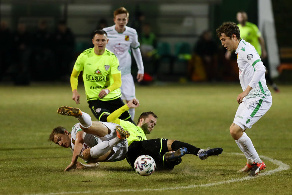 In this photo taken on Saturday, March 28, 2020, Gorodeya's Sergei Usenya, bottom left, and Shakhter's Igor Ivanovich, bottom right, fight for the ball during the Belarus Championship soccer match between Gorodeya and Shakhter in the town of Gorodeya, Belarus. Longtime Belarus President Alexander Lukashenko is proudly keeping soccer and hockey arenas open even though most sports around the world have shut down because of the coronavirus pandemic. The new coronavirus causes mild or moderate symptoms for most people, but for some, especially older adults and people with existing health problems, it can cause more severe illness or death. (AP Photo/Sergei Grits)