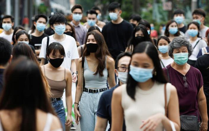 FILE PHOTO: People cross a street at the shopping district of Orchard Road as the city state reopens the economy, amid the coronavirus disease (COVID-19) outbreak, in Singapore