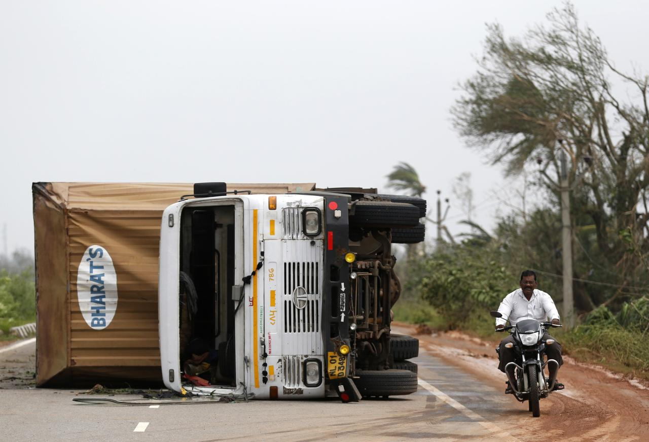 A man rides his motorbike past an overturned vehicle after Cyclone Phailin hit Gopalpur in Ganjam district in the eastern Indian state of Odisha October 13, 2013. India's strongest storm in 14 years left a trail of destruction along the country's east coast on Sunday, but little loss of life was reported after close to a million people took refuge in shelters. Cyclone Phailin was expected to dissipate within 36 hours, losing momentum as it headed inland after making landfall on Saturday from the Bay of Bengal, bringing winds of more than 200 kph (125 mph) to rip up homes and tear down trees. REUTERS/Ahmad Masood (INDIA - Tags: ENVIRONMENT DISASTER TRANSPORT)