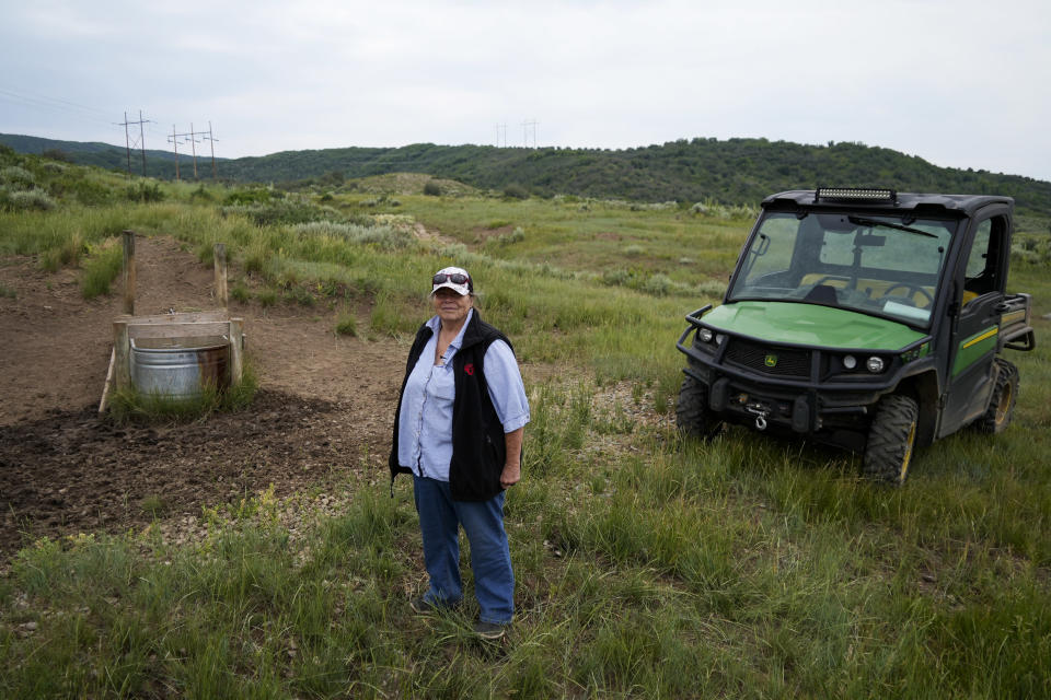 Jo Stanko, who along with her husband, Jim Stanko, are third-generation cattle ranchers, poses for a photo next to a spring used to water cattle on their ranch, Tuesday, July 13, 2021, near Steamboat Springs, Colo. Due to extreme drought conditions this year, Jim Stanko says he may have to sell some of their herd if he can't harvest enough hay to feed them. (AP Photo/Brittany Peterson)