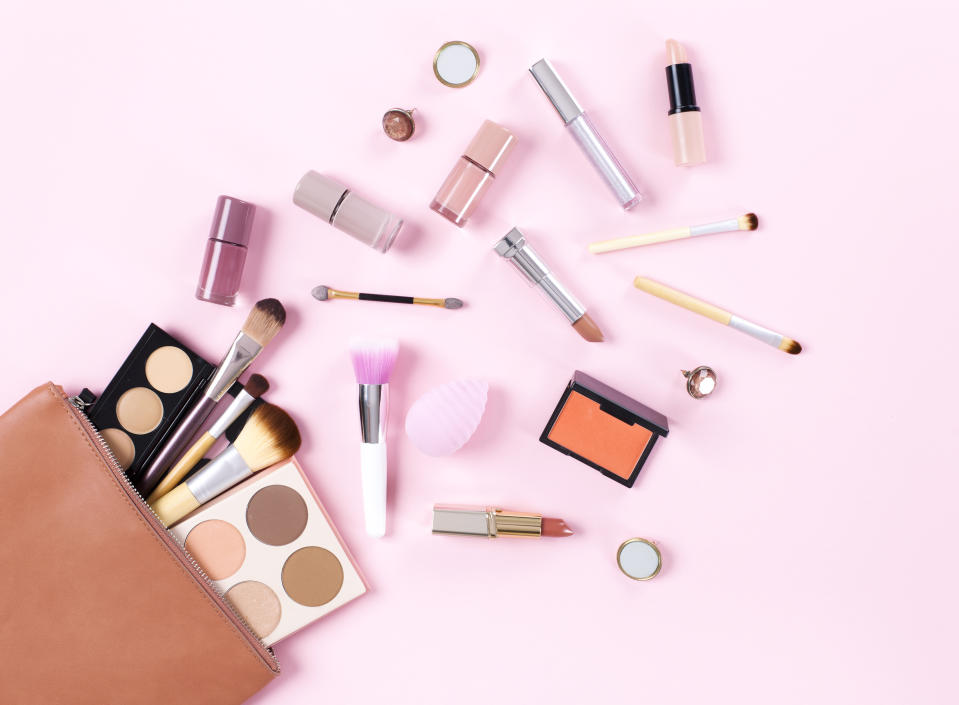 Makeup bag with cosmetic products spilling out on to a soft pink background