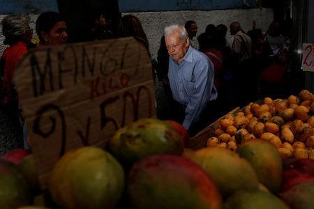 A man walks past people queueing to try and buy food outside a supermarket in Caracas, Venezuela May 23, 2016. REUTERS/Carlos Garcia Rawlins