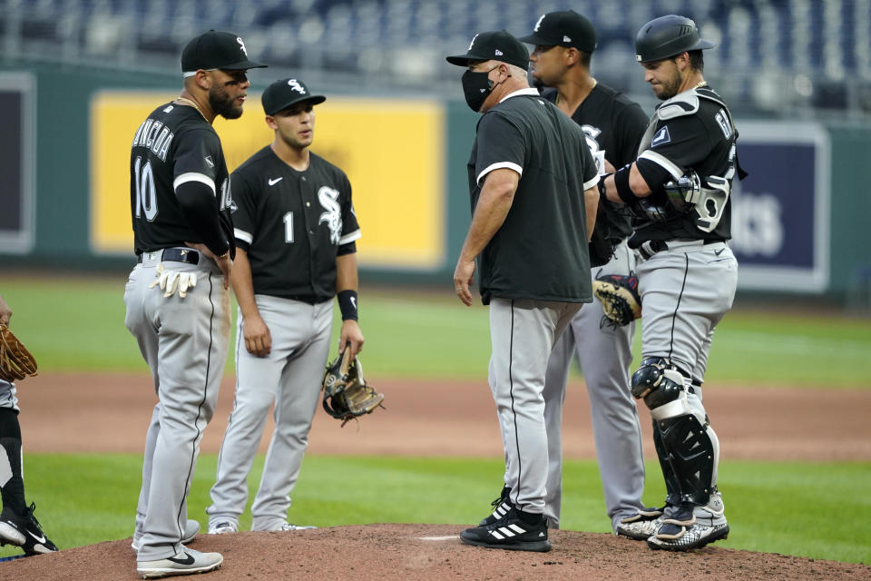 Chicago White Sox manager Rick Renteria talks to his players during a pitching change in the fourth inning of the team's baseball game against the Kansas City Royals on Saturday, Aug. 1, 2020, in Kansas City, Mo. (AP Photo/Charlie Riedel)