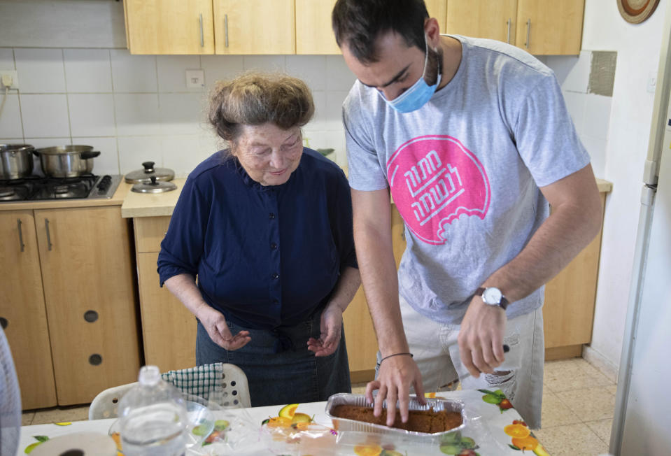 Sonia Rozenblatt, 85, tastes a cake made for her by Israeli volunteer Din Belz in the central Israeli city of Ra'anana, Thursday, Oct. 8, 2020. For thousands of older Israelis like Rozenblatt, being housebound alone during Israel's second nationwide lockdown due to the coronavirus pandemic is difficult and depressing. But each week ahead of the Jewish Sabbath, which starts on Friday at sundown, a home-baked cake is delivered by one of thousands of volunteers bringing pastries to home-bound older Israelis. (AP Photo/Sebastian Scheiner)