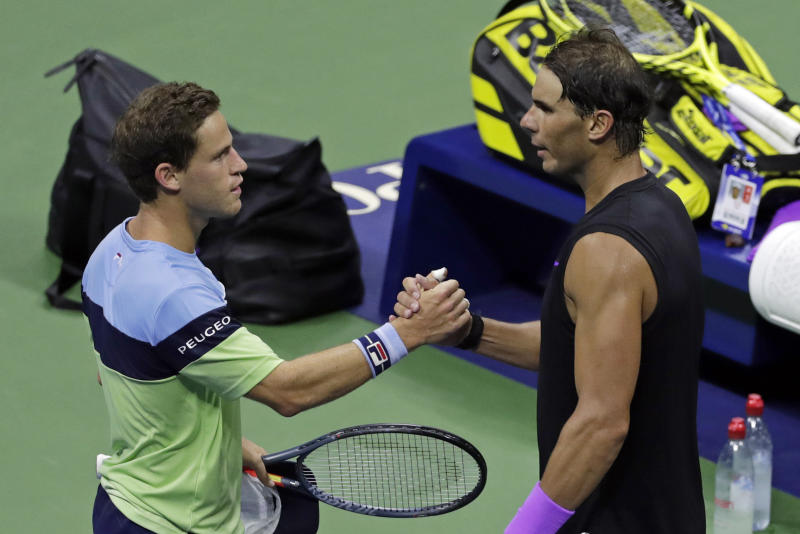 Diego Schwartzman, left, of Argentina, clasps hands with Rafael Nadal, of Spain, after Nadal defeated Schwartzman during the quarterfinals of the U.S. Open tennis tournament early Thursday, Sept. 5, 2019, in New York. (AP Photo/Adam Hunger)