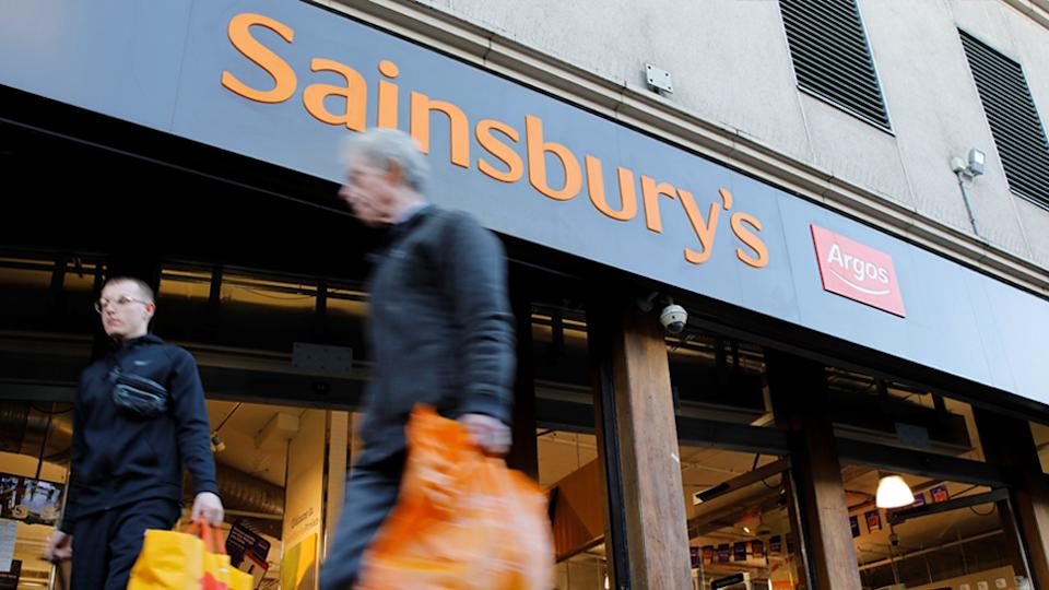 Men walk past Sainsbury's and Argos