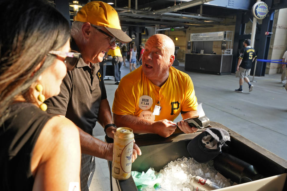 Tom Congdon, center, a vendor at Pittsburgh sports venues for 38 years, mans his beer and water cart in the concourse at PNC Park for a baseball game between the Pittsburgh Pirates and the Atlanta Braves in Pittsburgh, Monday, July 5, 2021. With fans back in the stands and concessions being sold, ballpark employees have had a chance to return after the pandemic hit many of them hard. (AP Photo/Gene J. Puskar)