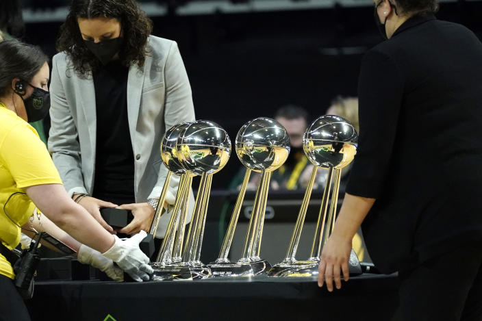 Workers reach to remove the four Seattle Storm championship trophies before a WNBA basketball game against the Las Vegas Aces Saturday, May 15, 2021, in Everett, Wash. The Storm won the 2020 championship. (AP Photo/Elaine Thompson)