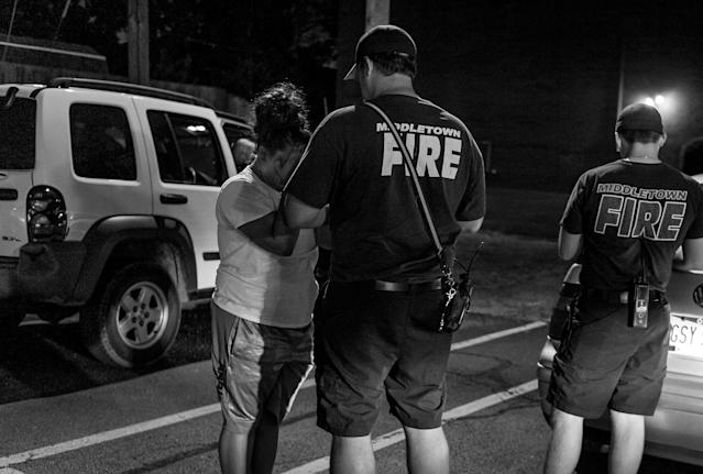 "The Middletown Fire Department responds to a call about a young woman possibly overdosing on heroin. ""You're not going to get in trouble:"" A fireman tries to convince her to go to the hospital. (Photograph by Mary F. Calvert for Yahoo News)"