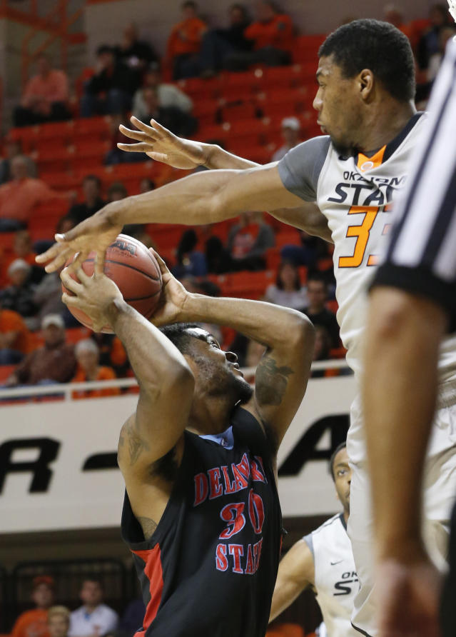 Oklahoma State guard Marcus Smart, right, jumps up to attempt to block a shot by Delaware State guard Jordan Lawson, left, in the first half of an NCAA college basketball game in Stillwater, Okla., Tuesday, Dec. 17, 2013. (AP Photo/Sue Ogrocki)