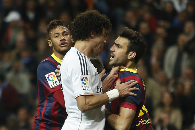 Real's Pepe, centre, reacts with Barcelona's Cesc Fabregas, centre right, as Fabregas celebrates Lionel Messi's goal, during a Spanish La Liga soccer match between Real Madrid and FC Barcelona at the Santiago Bernabeu stadium in Madrid, Spain, Sunday, March 23, 2014. (AP Photo/Andres Kudacki)