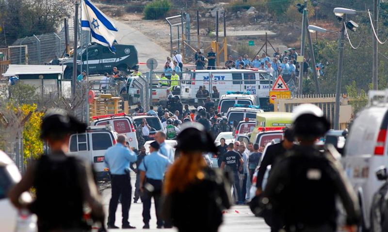 Israeli security personnel and emergency services gather at the site of an attack at the entrance to the West Bank settlement of Har Adar.
