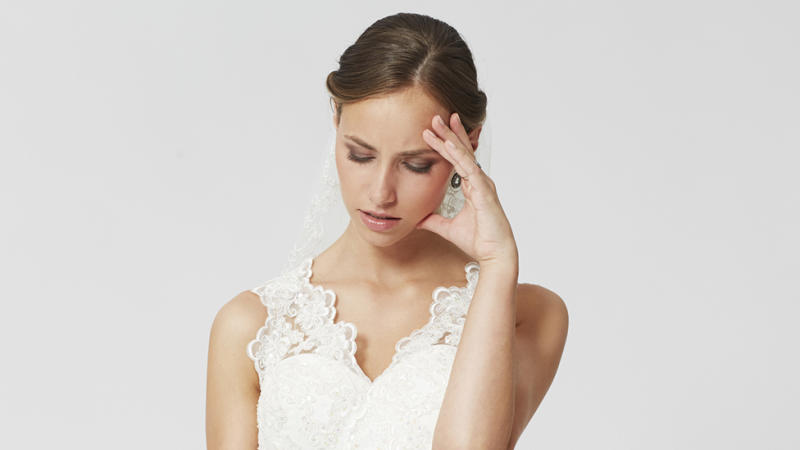 Bride hold head in stock image representing her decision to cancel a destination wedding and leave guests out of pocket