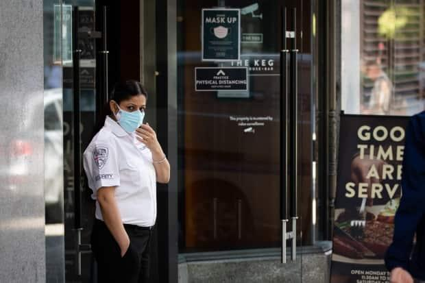 A masked security guard stands outside a Vancouver restaurant on Sept. 7.  (Maggie MacPherson/CBC News - image credit)