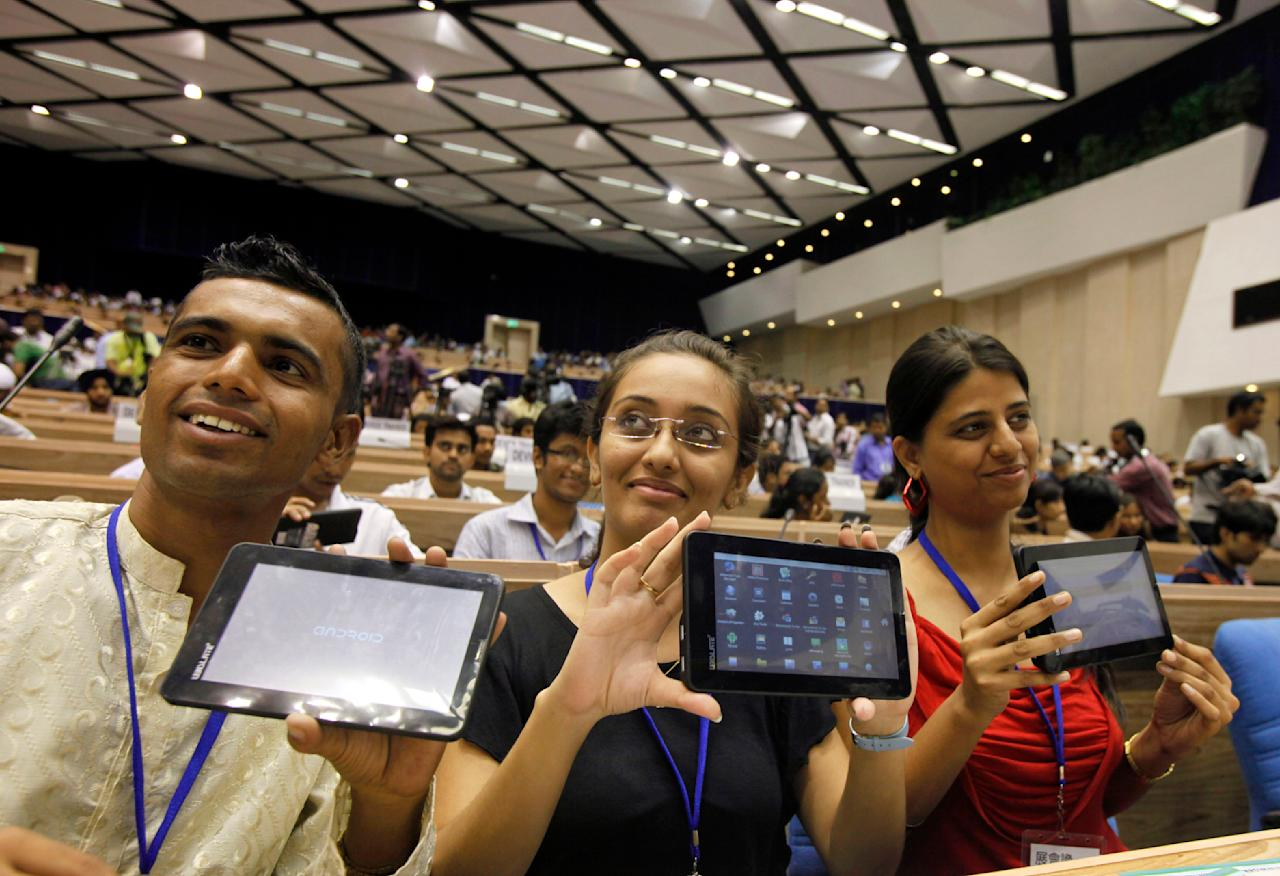 "Indian students pose with the supercheap 'Aakash' Tablet computers which they received during its launch in New Delhi, India, Wednesday, Oct. 5, 2011. The $35 basic touchscreen tablet aimed at students can be used for functions like word processing, web browsing and video conferencing. 'Aakash' , manufactured by DataWind has a 7""Android 2.2 touch screen and a HD video co-processor. The Indian government intends to deliver 10 million tablets to students across India. (AP Photo/Gurinder Osan)"