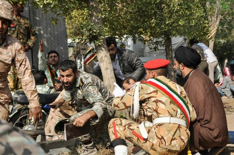 Soldiers and a Muslim cleric take cover during an attack on a military parade in the Iranian city of Ahvaz on September 22, 2018