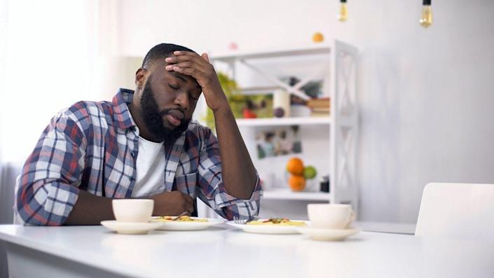 Tired African-American man having headache after hard day, feeling exhausted